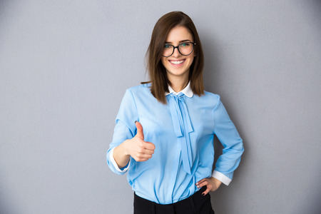 Happy businesswoman showing thumb up over gray background. Wearing in blue shirt and glasses. Looking at camera Stockfoto