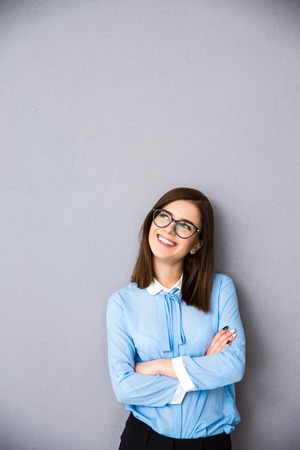 arm: Smiling businesswoman with arms folded looking up at copyspace. Standing over gray background. Wearing in blue shirt and glasses