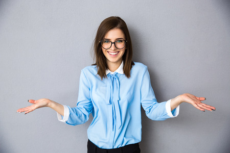 灰色の背景の上を求めてのジェスチャーの笑みを浮かべて女性実業家。カメラを見ています。青いシャツとメガネの着用