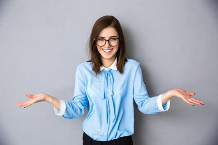 회색 배경 위에 묻는 제스처에 웃는 사업가. 카메라를 찾고. 파란 셔츠와 안경 착용 스톡 콘텐츠