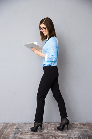 black pants: Full length portrait of a businesswoman with cup of coffee and tablet computer. Wearing in black pants and blue shirt.
