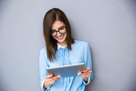 vasos: Feliz empresaria de pie con el ordenador de mesa sobre fondo gris. El uso en camisa azul y gafas.