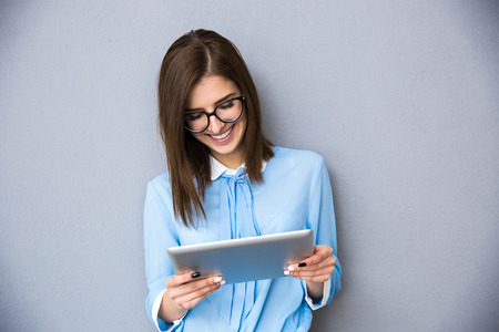 Happy businesswoman standing with table computer over gray background. Wearing in blue shirt and glasses. Stock Photo
