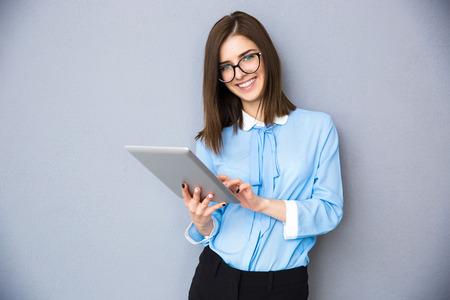 タブレット コンピューターに灰色の背景上に立って笑顔の実業家。青いシャツとメガネを着用します。カメラを目線