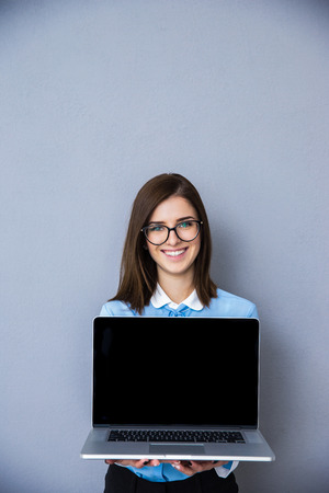 Glimlachende onderneemster met lege laptop scherm over grijze achtergrond. Kijkend naar de camera. Het dragen van een bril en blauw overhemd
