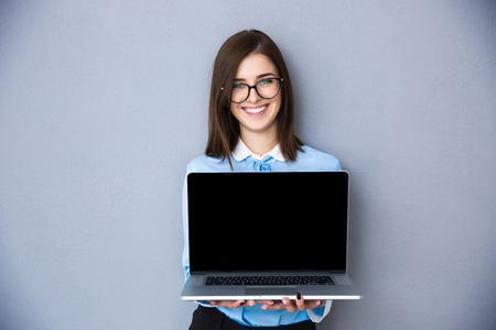 회색 배경 위에 빈 노트북 화면을 보여주는 행복 한 사업가. 파란색 셔츠와 안경 착용. 카메라를 찾고 스톡 콘텐츠