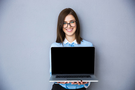Happy businesswoman showing blank laptop screen over gray background. Wearing in blue shirt and glasses. Looking at camera