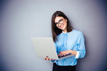 서 서 회색 배경 위에 노트북을 사용 하여 웃는 사업가. 파란색 셔츠와 안경 착용. 카메라를 보면서