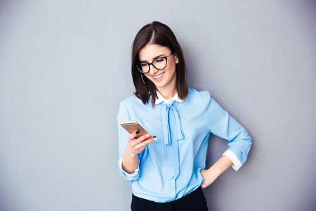 sms: Smiling businesswoman using smartphone over gray background. Wearing in blue shirt and glasses.