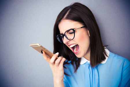 phone isolated: Angry businesswoman shouting on smartphone. Wearing in blue shirt and glasses. Standing over gray background Stock Photo