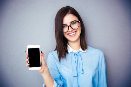 회색 배경 위에 빈 스마트 폰 화면을 보여주는 웃는 사업가. 파란색 셔츠와 안경 착용. 카메라를 찾고. 스톡 콘텐츠