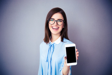 Laughing businesswoman showing blank smartphone screen over gray background. Wearing in blue shirt and glasses. Looking at camera. Archivio Fotografico
