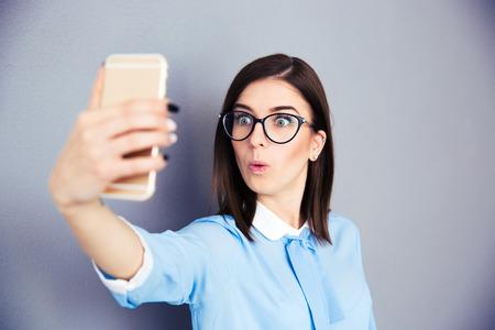 surprised: Empresaria sorprendida haciendo selfie foto en smartphone. El uso en camisa azul y gafas. De pie sobre fondo gris
