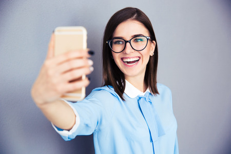 Laughing businesswoman making selfie photo on smartphone. Wearing in blue shirt and glasses. Standing over gray background photo
