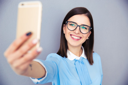 sexy photo: Smiling businesswoman making selfie photo on smartphone. Wearing in blue shirt and glasses. Standing over gray background