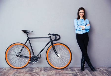 Cheerful young businesswoman with arms folded standing near bicycle. Looking at camera Stock Photo
