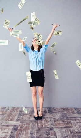 Business woman standing in the rain of the dollar bills looking very happy. Wearing in blue shirt, black dress and glasses. photo