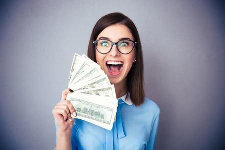 Lachende onderneemster die rekeningen van de dollar en schreeuwen over grijze achtergrond. Het dragen van in het blauwe shirt en glazen. Kijkend naar de camera Stockfoto