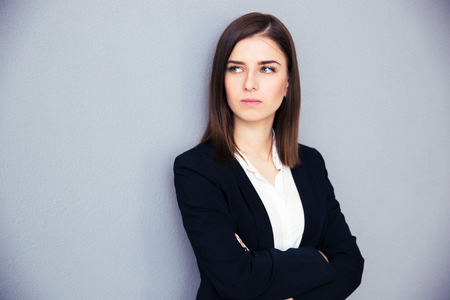 arm: Young serious businesswoman with arms folded standing over gray background. Looking away Stock Photo