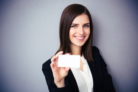 representing: Woman holding blank card over gray background. Focus on woman. Looking at camera