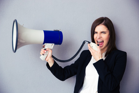 Young businesswoman shouting with megaphone over gray background. Looking at camera.