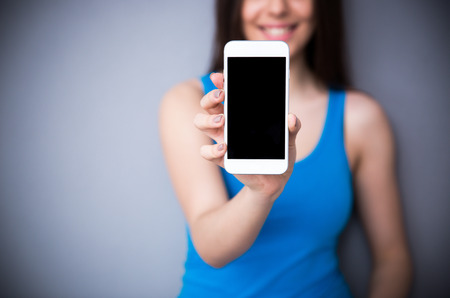 hold: Happy woman showing blank smartphone screen over gray background. Focus on smartphone. Stock Photo