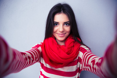 회색 배경 위에 행복 귀여운 여자 만들기 셀카. 밝은 스카프와 스웨터를 입고. 카메라를 찾고