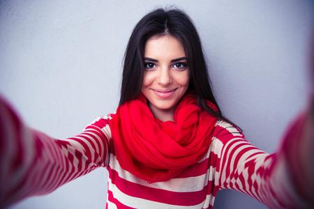 Feliz mujer toma selfie lindo sobre fondo gris. El uso de bufanda brillante y suéter. Mirando a la cámara