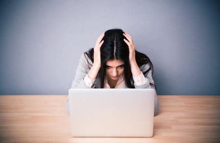 mujer trabajadora: Empresaria cansada sentado en la mesa sobre fondo gris. Buscando en la computadora portátil