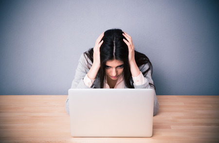 stressed woman: Tired businesswoman sitting at the table over gray background. Looking on laptop