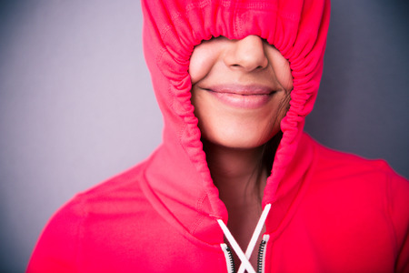 energized: Portrait of a happy woman covering her eyes with hood over gray background