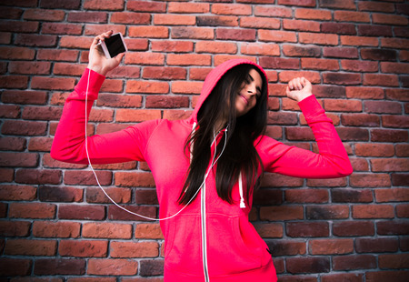 Smiling young girl listening music and dancing in headphones over brick wall photo