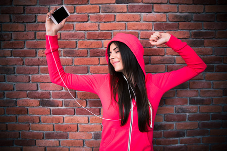 dance: Happy woman listening music and dancing in headphones over brick wall Stock Photo
