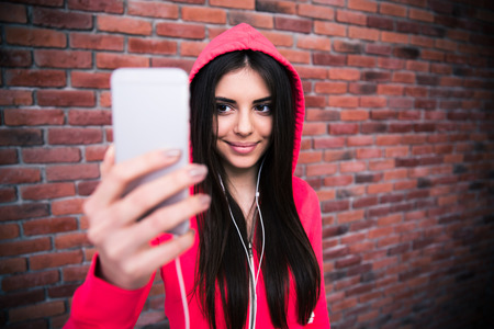 Smiling woman making selfie photo over brick wall. Looking on smartphone photo