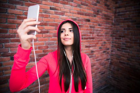 Happy young sportive woman making selfie photo with smartphone over brick wall photo