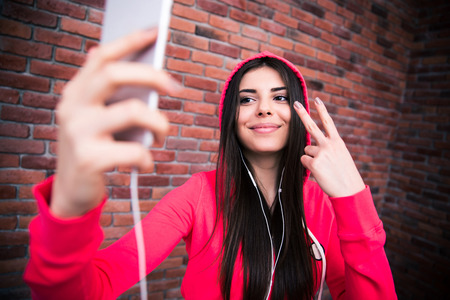 Happy beautiful woman making selfie photo on smartphone. Wearing in sportive cloth. Standing over brick wall photo