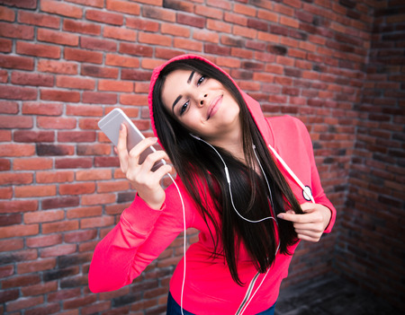 Happy sportive cute woman listening music on smartphone over brick wall photo