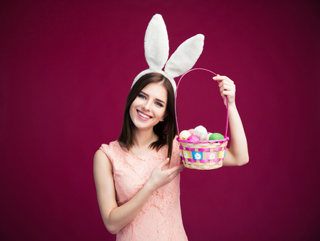 Happy young woman with an Easter egg basket over pink background. Looking at camera