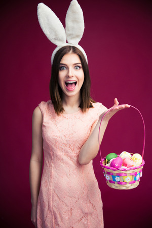 Cheerful young woman with bunny ears and Easter egg basket. Looking at camera. Standing over pink background.