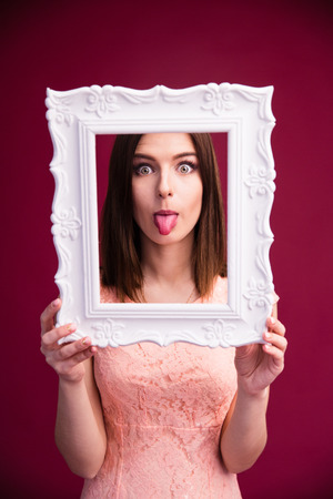 looking through frame: Woman showing her tongue and looking through frame over pink background Stock Photo