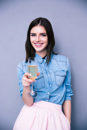 Cute attractive woman with glass of champagne over gray background. Looking at camera. photo