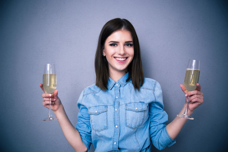 Smiling woman holding two glass of champagne over gray background. Looking at camera photo