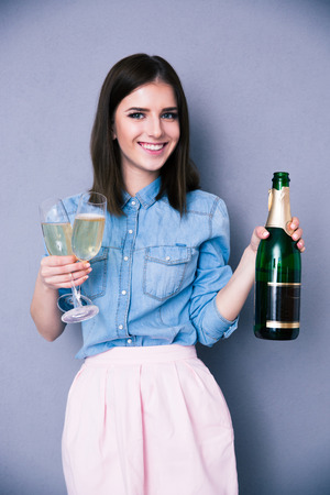 Smiling woman holding two glass with bottle of champagne over gray background. Looking at camera photo