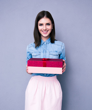 Smiling woman holding gift and looking at camera over gray background. Looking at camera