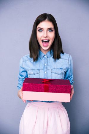 Verraste vrouw bedrijf geschenk en het kijken op de camera over grijze achtergrond Stockfoto
