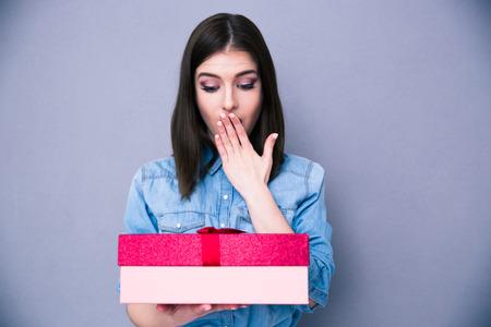 Surpris jeune femme debout avec un cadeau sur fond gris. En regardant sur cadeau. Se couvrir la bouche avec sa main Banque d'images