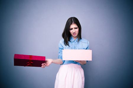 nespokojen: Nespokojený žena otevření dárek nad šedé pozadí