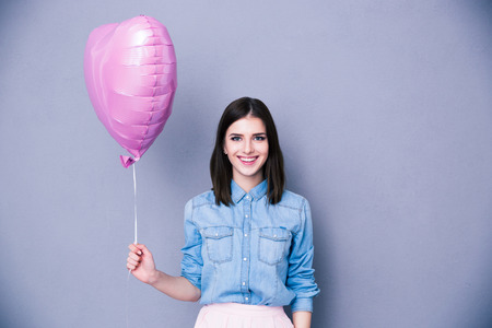 heart balloon: Smiling woman holding balloon and looking at camera over gray background.