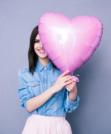 globo: Mujer sonriente que cubre su ojo con el globo en forma de coraz�n sobre fondo gris. Mirando a la c�mara Foto de archivo