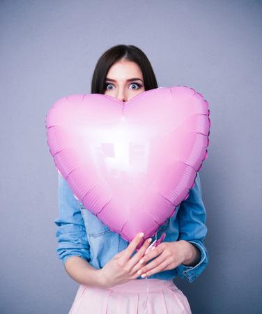 gray background: Portrait of a woman holding heart shaped balloon over gray background. Looking at camera Stock Photo